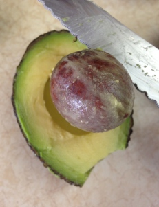 Remove the pit by holding the avocado cut-side up in one hand and (very carefully) thrusting your knife's broad side into the center of the pit with the other.