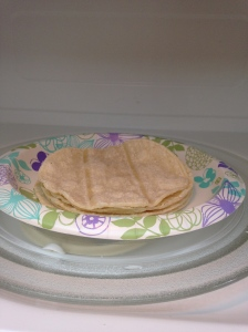 Microwaving the corn tortillas to make them pliable.